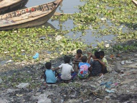 Kids sitting along the riverside